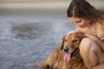 Close up of young woman in bikini stroking her Golden Retriever dog at the beach — Stock Photo