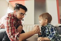 Father and son arm wrestling at home — Stock Photo