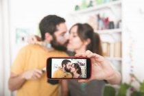 Junges paar küssen und dabei ein Selbstporträt mit Pinsel — Stockfoto