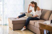 Sonriente joven sentada en el sofá con el ordenador portátil - foto de stock