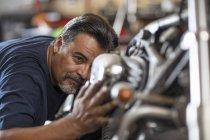 Motocicleta mecânica examinando moto na oficina — Fotografia de Stock