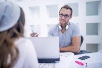 Homme avec ordinateur portable ayant une réunion avec une femme au bureau — Photo de stock