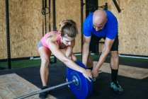 Man and woman preparing barbell in gym — Stock Photo