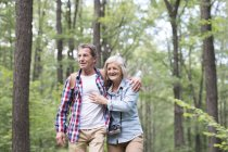 Happy cute senior couple hugging and walking in park — Stock Photo
