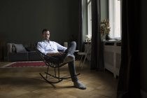 Portrait of man sitting on rocking chair in living room — Stock Photo