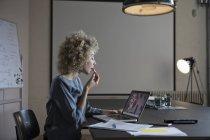 Mujer en la oficina aplicando maquillaje y el uso de monitor portátil como espejo - foto de stock