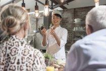 Літня пара уважно слухає шеф-кухаря в приготуванні їжі клас — стокове фото