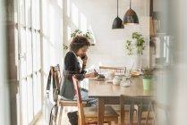 Молода жінка працює в кафе і розмовляти по телефону — стокове фото