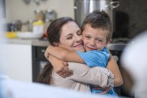 Caucasian cute mother and son hugging at kitchen — Stock Photo