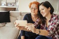 Матері і дорослі дочки беручи selfie на смарт-телефон, сидячи на дивані — стокове фото