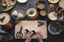 Femelle mains préparation Onigiris sushi, vue de dessus — Photo de stock