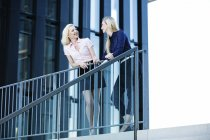 Two businesswomen talking standing by the building stairs — Stock Photo