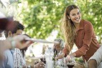 Mulher jovem sorridente, servindo-à mesa de almoço — Fotografia de Stock