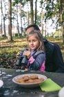 Bambina con binocolo rilassante con il padre in una foresta — Foto stock