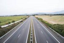 Leere Autobahn und grünen Wiesen Landschaft — Stockfoto