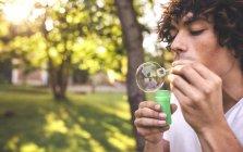 Молодой человек пускает мыльные пузыри в парке — стоковое фото