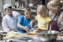 Kids getting practical in cooking class — Stock Photo