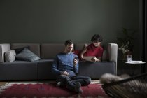 Couple relaxing together in the living room with electronic devices — Stock Photo