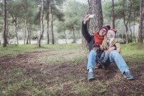 Vater und Sohn nehmen ein Selbstporträt mit Smartphone im Wald — Stockfoto