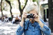 Веселая взрослая женщина, снимающая на камеру на размытом фоне — стоковое фото