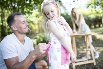Father tying girls apron in garden — Stock Photo
