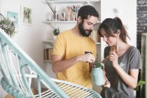 Young couple painting wicker armchair at home — Stock Photo