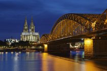 Germany, Cologne, lighted Cologne Cathedral and Hohenzollern Bridge — Stock Photo