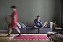 Hombre sentado en el sofá en la sala de estar, mientras que la mujer que pasa en primer plano - foto de stock