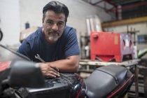 Motorrad-Mechaniker arbeiten in Werkstatt und Blick in die Kamera — Stockfoto