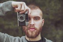 Ritratto di uomo barbuto che scatta foto con fotocamera vintage — Foto stock