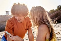 Couple checking cell phone on the beach — Stock Photo