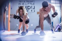 Young man and woman doing dumbbell press ups in gym — Stock Photo