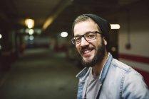 Retrato de homem casual em uma garagem a sorrir — Fotografia de Stock