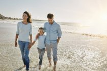 Portrait of smiling family strolling on beach — Stock Photo