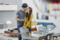 Portrait of couple kissing in furniture store — Stock Photo