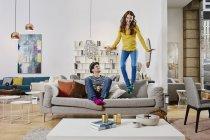 Retrato de mulher pulando no sofá na loja de móveis — Fotografia de Stock