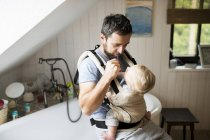 Father with baby in baby carrier brushing his teeth — Stock Photo