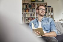 Laughing man sitting with book on couch in living room — Stock Photo