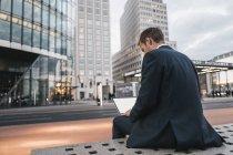 Германия, Берлин, Потсдамская площадь, вид сзади бизнесмена, сидя на скамейке, используя ноутбук вечером — стоковое фото