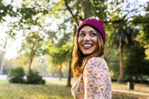 Giovane donna felice che indossa cappello di lana in un parco in autunno — Foto stock