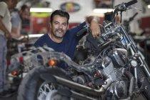 Sorrindo motocicleta mecânico na oficina olhando para a câmera — Fotografia de Stock