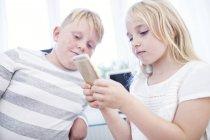 Frère et sœur utilisant le téléphone cellulaire ensemble — Photo de stock