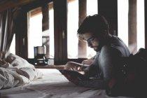 Портрет молодої людини за допомогою планшетного ПК на ліжку — стокове фото