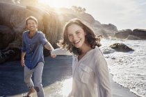 Happy couple walking hand in hand on the beach — Stock Photo