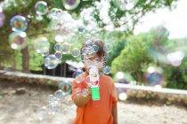 Kleiner Junge spielt mit Seifenblasenmaschine — Stockfoto
