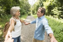 Couple de personnes âgées mignon actif main dans la main avec le spectateur dans le parc — Photo de stock