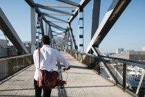 Vue arrière de l'homme en poussant le vélo sur le pont — Photo de stock