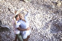 Elevated view of active cute senior couple hugging together on beach — Stock Photo