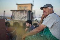 Профессиональные кавказские рыбаки, сидящие в гавани на закате — стоковое фото