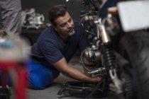 Mecânica motocicleta concentrada trabalhando em oficina — Fotografia de Stock